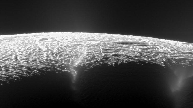 Enceladus'un yüzeyindeki çatlaklardan su buharı yükseliyor. [NASA]