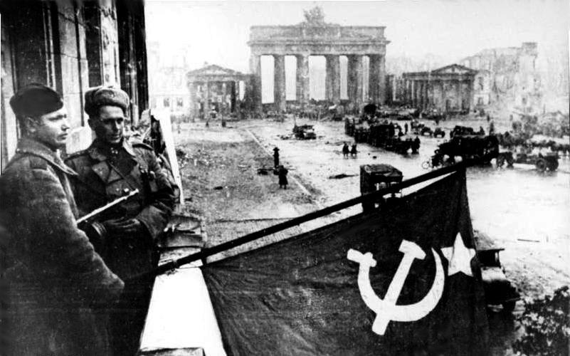 Berlin'deki Adlon Oteli'nin balkonundan Sovyet bayrağı sarkıtan Rus askerleri. [Wikipedia]