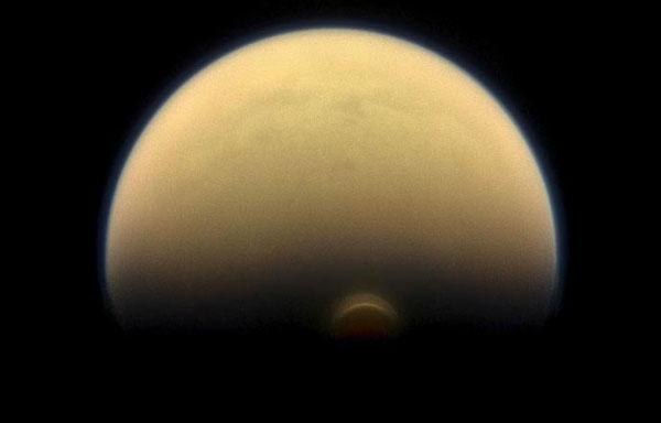 Cassini tarafından 2013'te çekilen fotoğraf, Satürn'ün ortasında nokta gibi beliren Titan'ın güney kutup noktasındaki bulut oluşumunu gösteriyor.[NASA]